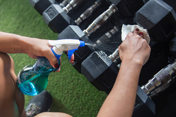 Woman cleaning dumbbells with cleaning spray