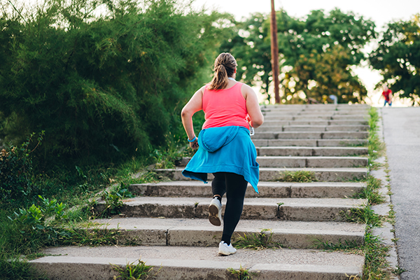 Woman outside running up steps
