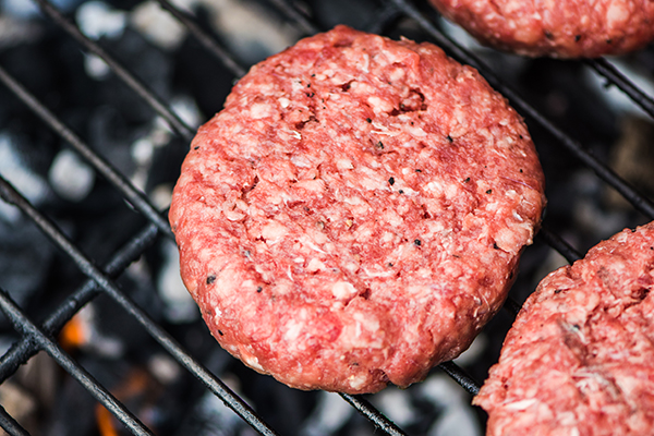 Raw burgers cooking on a grill