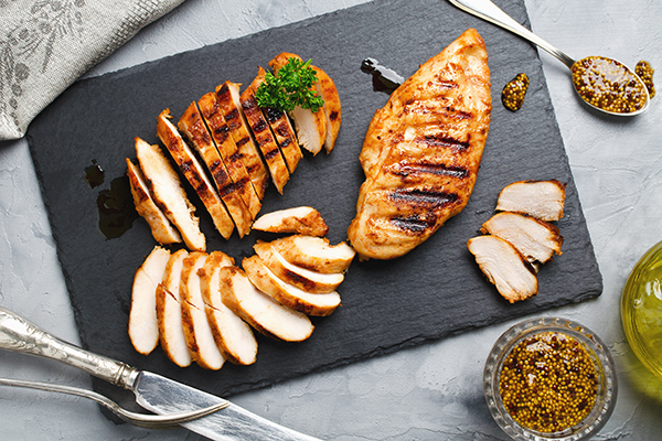 Grilled chicken fillets on plate.