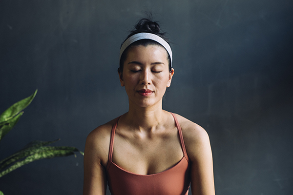 Woman meditating with eyes closed.