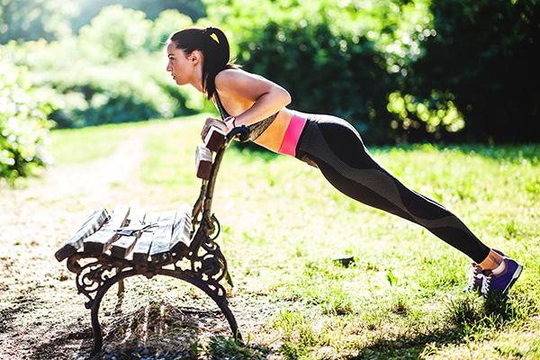 Femme faisant des pompes inclinées sur un banc de parc