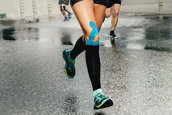 Photo recadrée d'un coureur avec du ruban KT sur le genou