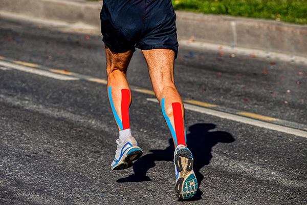Photo recadrée des jambes du coureur avec KT Tape