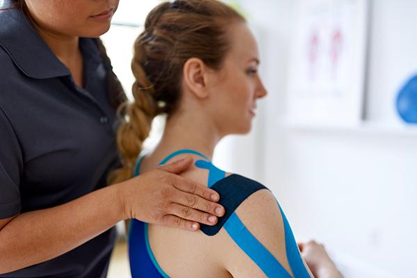 Une femme applique du ruban KT sur l'épaule de l'athlète