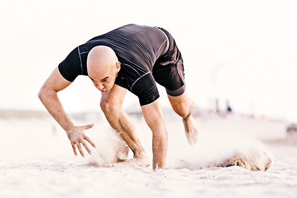 Man doing bear crawls on the beach
