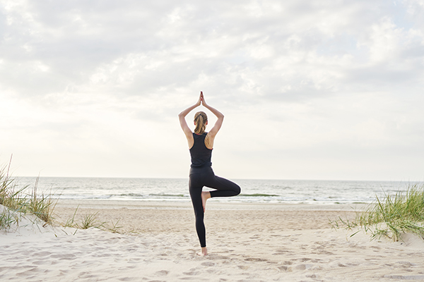 Woman in tree pose on the beach