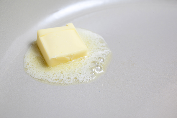 A tablespoon of butter melting in the pan.