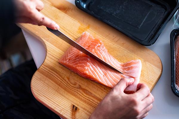 Woman slicing raw salmon on cutting board