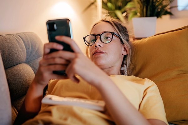 Woman lying on sofa looking at her phone