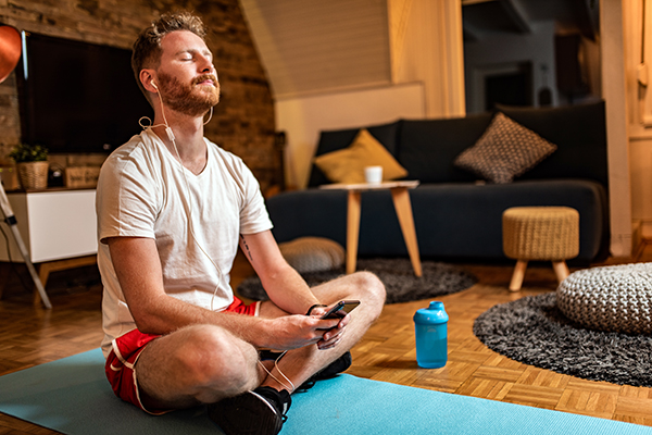 Man calming his mind with guided meditation on earphones at home.