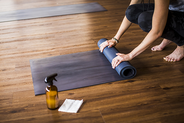 Woman cleaning, rolling up yoga mat