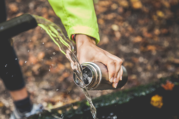 Closeup of woman's hand filling metal water bottle
