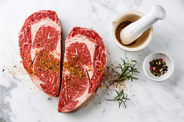 Seasoned raw steak on marble