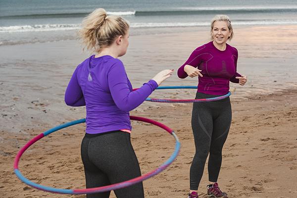 Women using weight hula hoop at a beach workout