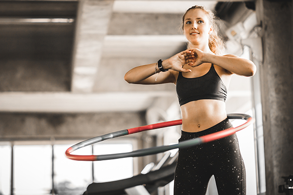 Woman using weight hula hoop in a gym