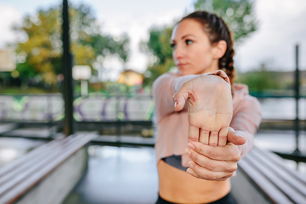 Woman stretching hands and wrist outdoors.