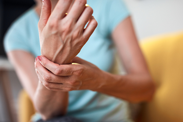 Woman with hand and arm pain at home.