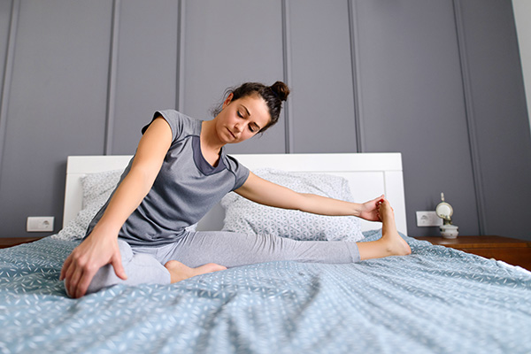 Woman stretching her leg in her bed early in the morning.
