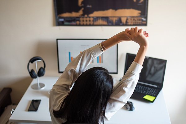 Woman stretching while working on computer from a home office