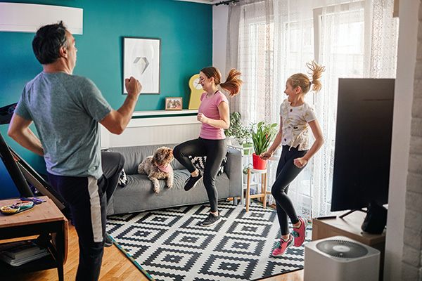 Father and two daughters exercising at home