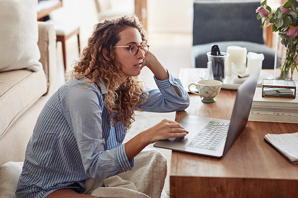 Woman looking at her laptop looking bored
