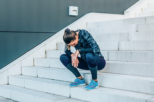 Tired female athlete sitting on stairs outside