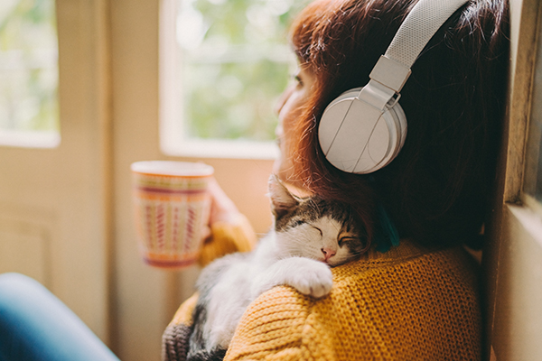 Woman listening to headphones, cuddling cat