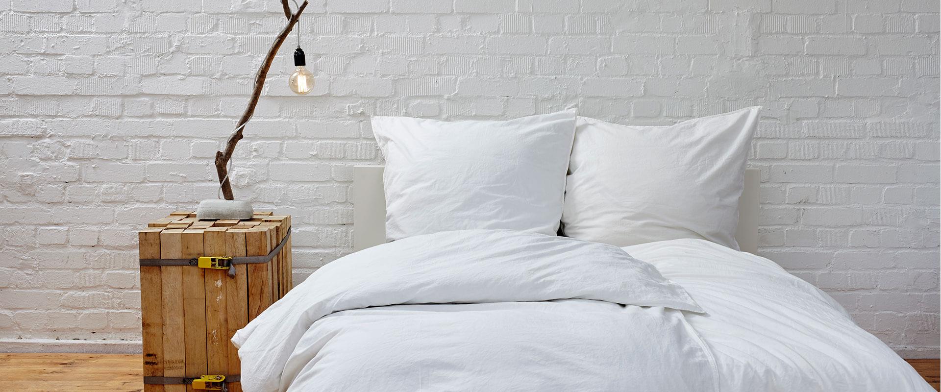 Habitación con ropa de cama color blanco y buró de madera.