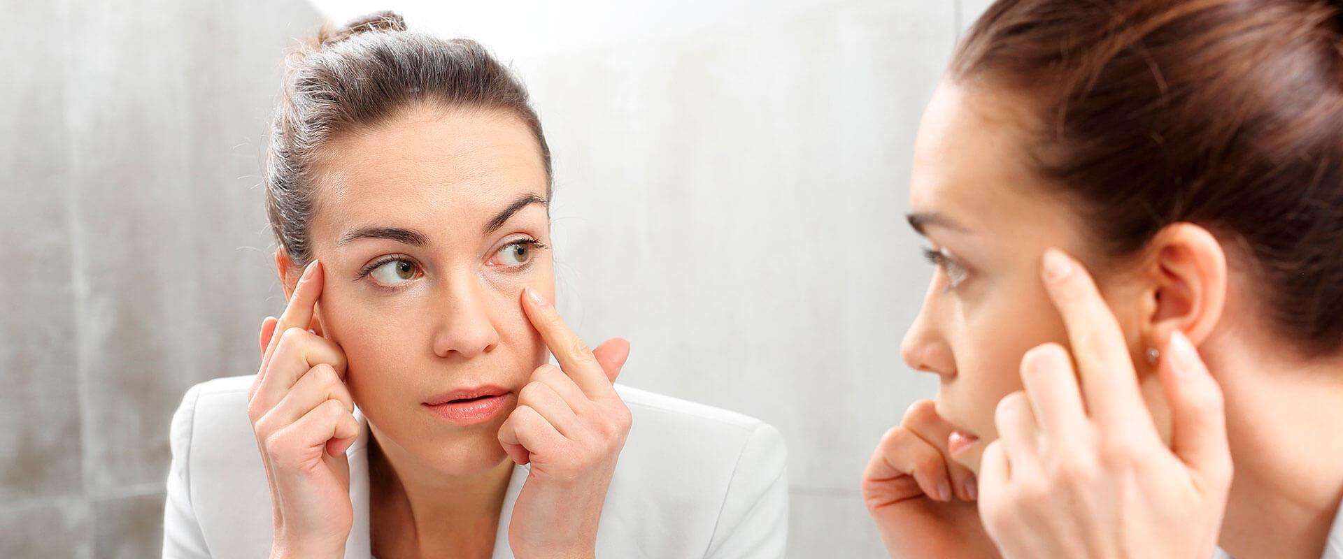 Mujer viéndose frente al espejo y tocándose las bolsas debajo de los ojos.
