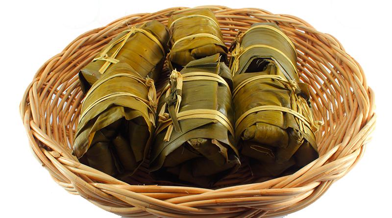 Canasta de mimbre con tamales envueltos en hojas de plátano.