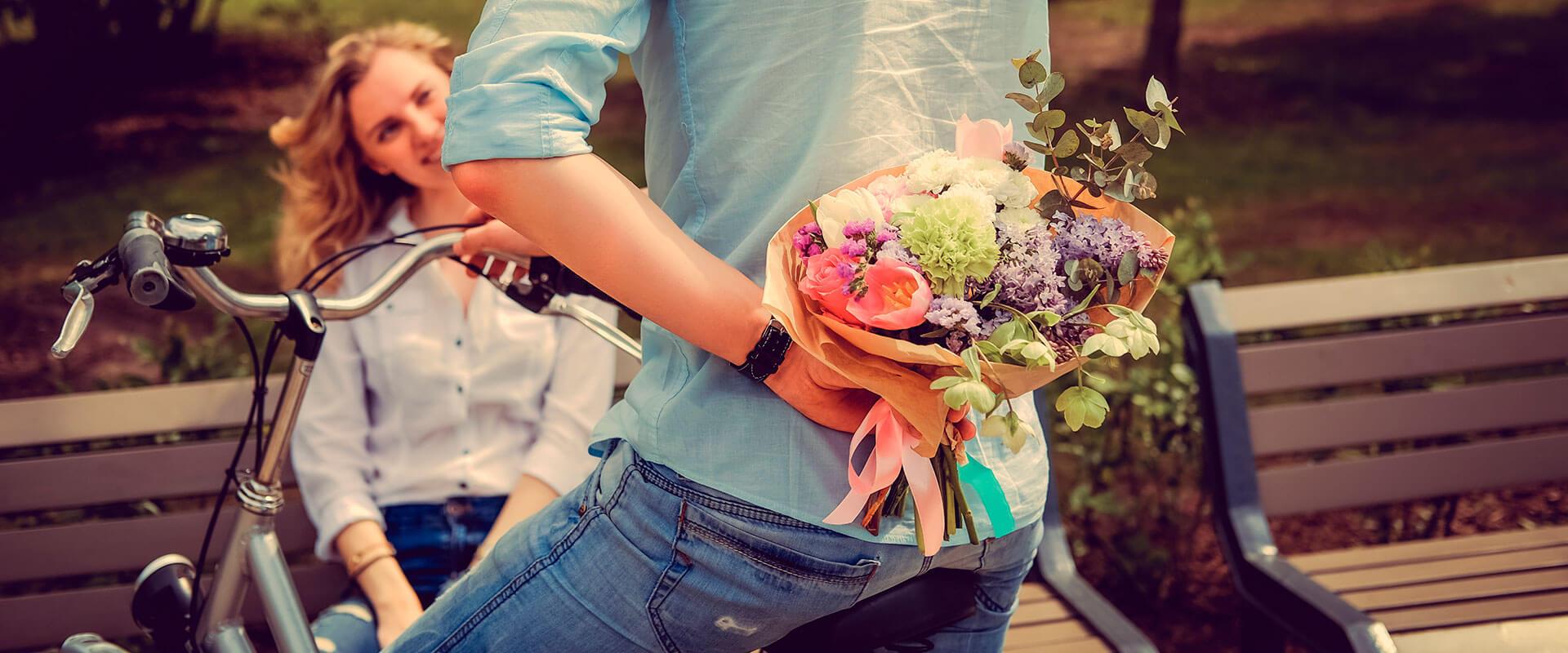 Hombre sorprendiendo a una mujer con un ramo de flores.