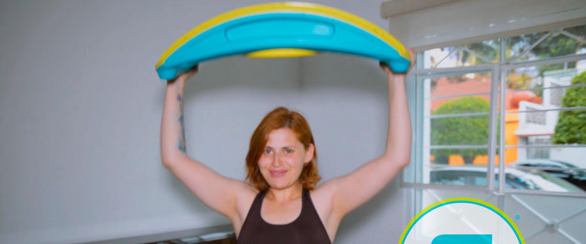 Mujer cargando el aparato de ejercicio llamado Gravity ABS.