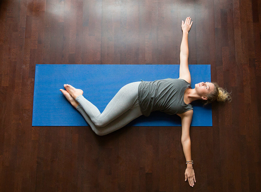 mujer-yoga-postura-torsion-almohada-soñare