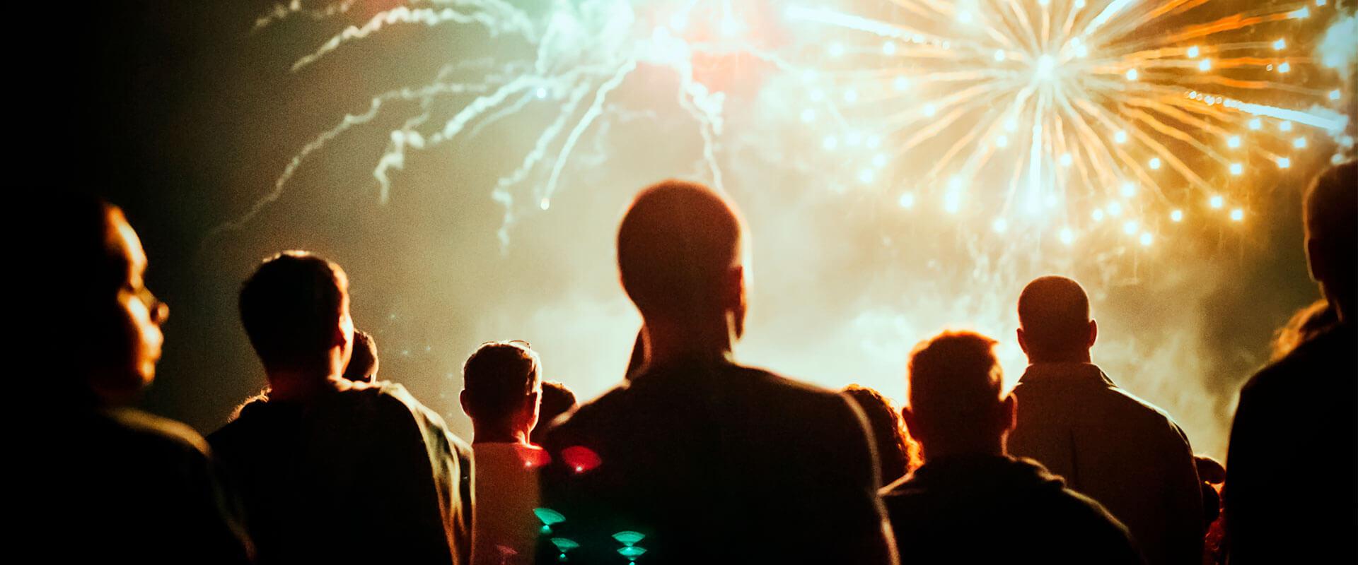 Personas viendo los fuegos artificiales en el cielo, durante la noche.
