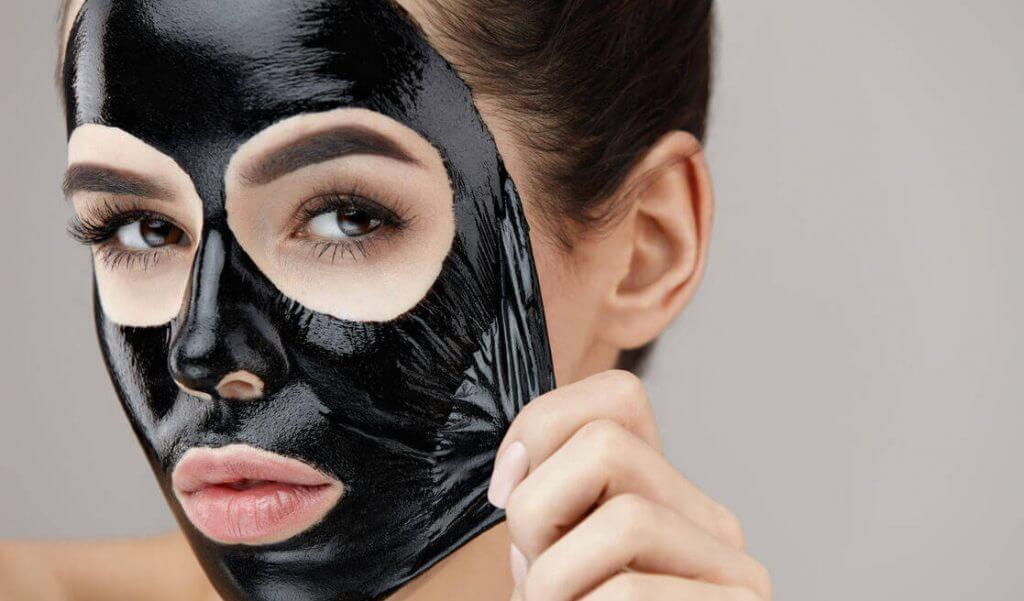 Mujer cuida de su piel con mascarilla de carbón activado