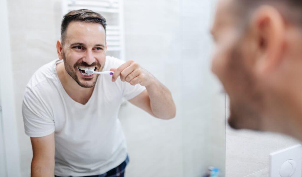 Hombre sin Ortosomnia lava sus  dientes antes de dormir