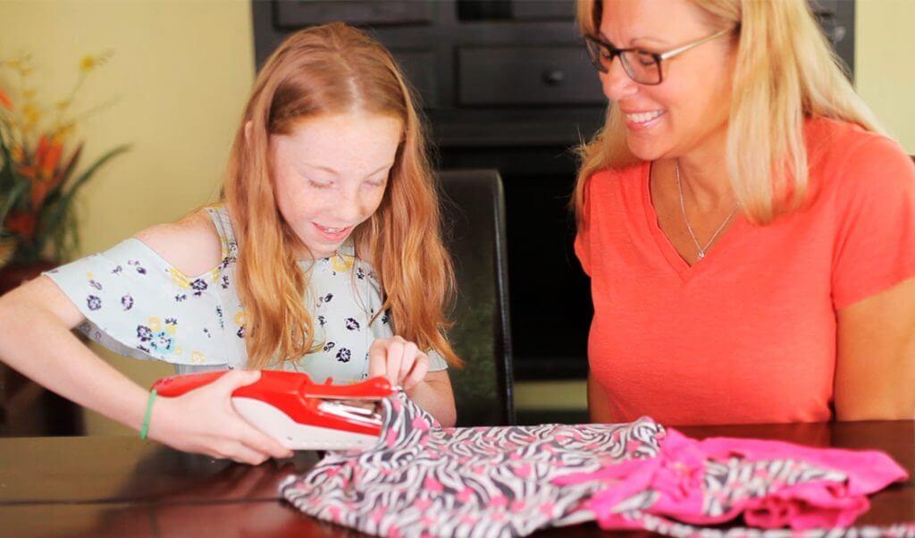 Madre e hija cosen con máquina portátil