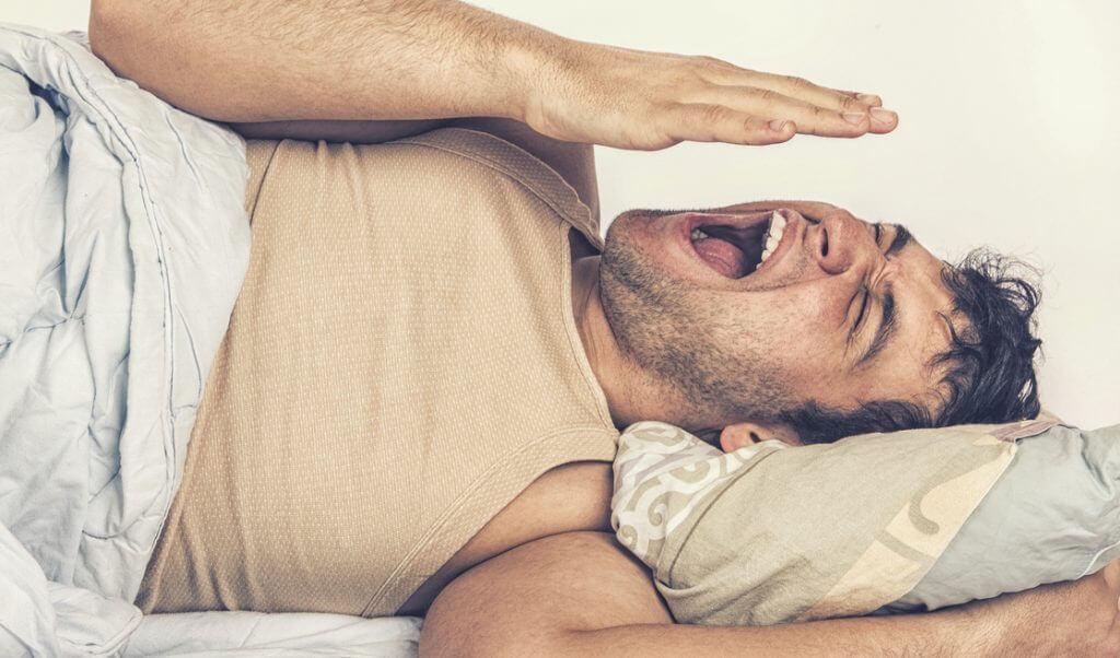 Hombre bosteza antes de dormir