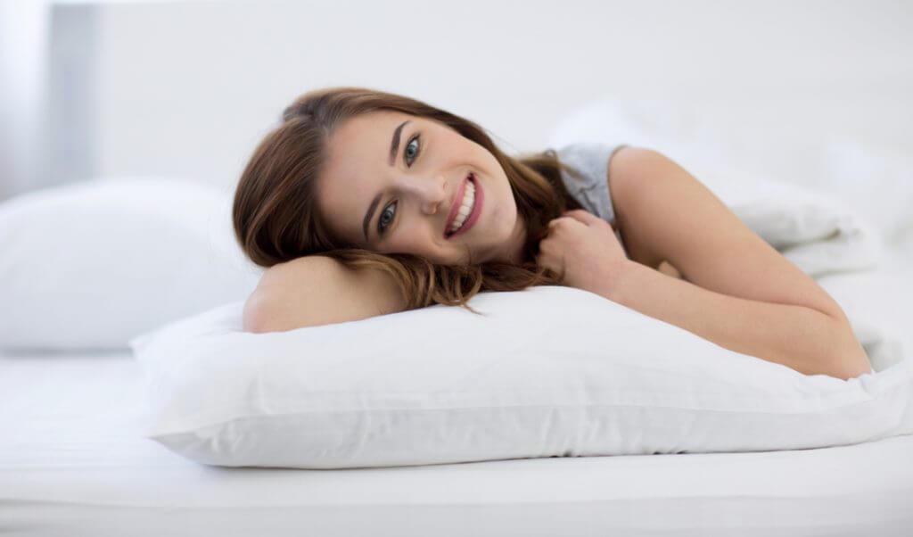 mujer feliz en cama tendida