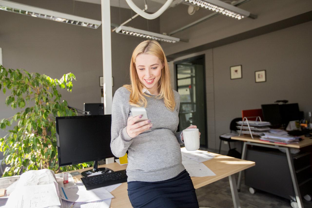 Gestante no ambiente empresarial, consultando direitos trabalhistas no celular