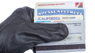 Identification documents (social security, driver license and credit cards) in hand of thief, isolated on white.