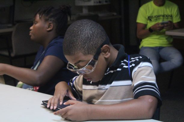 School Age student, Basil B., seen here working on an electronic tablet device