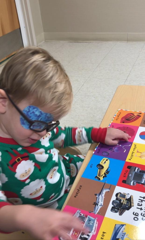 Early Intervention student, Matthew, feeling a tactile picture book