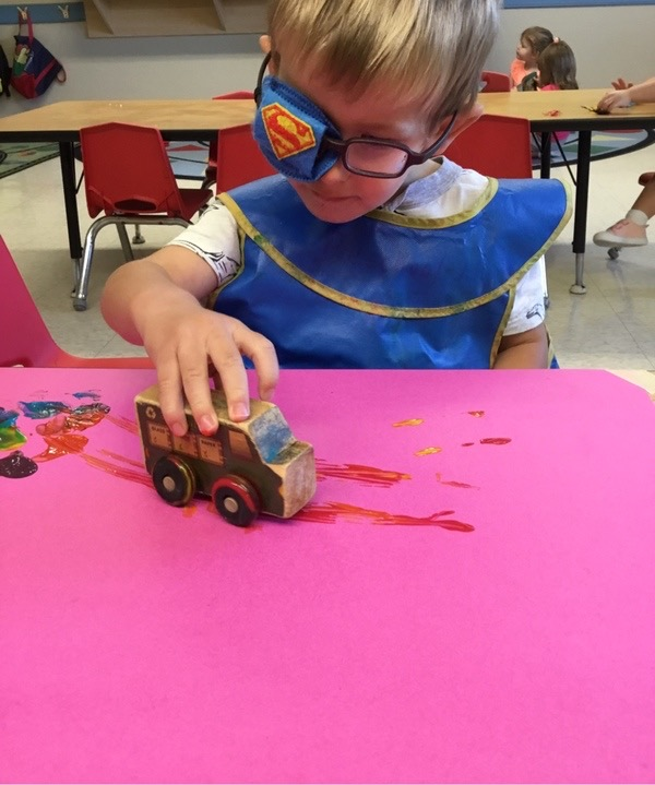 Early Intervention student, Matthew, playing with a wooden toy bus