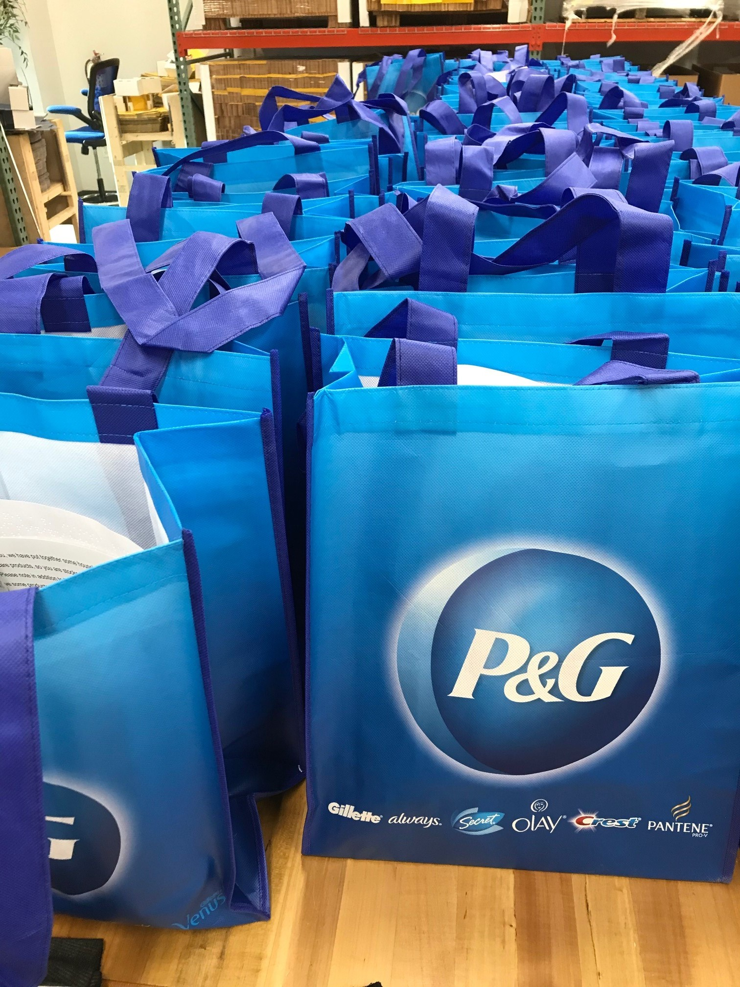 Image of P&G branded tote bags containing home cleaning and personal care products.