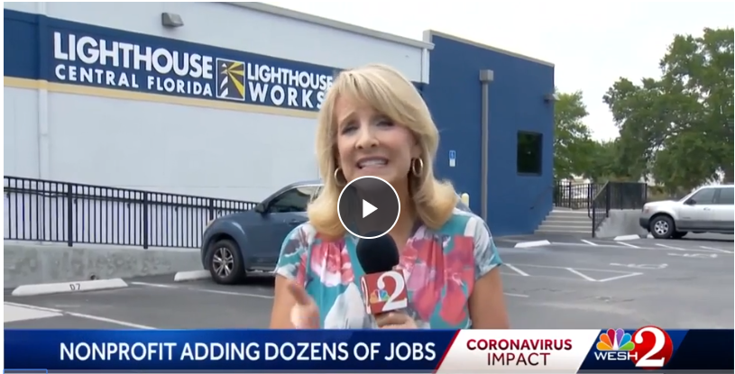 WESH 2 News reporter, Amanda Dukes, seen here holding microphone and reporting from outside the Lighthouse Works building in SODO