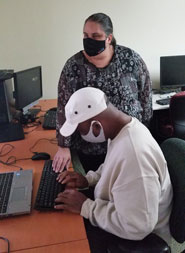 Anthony works with his Assistive Technology (AT)  instructor, Maurine Park, during an AT training.