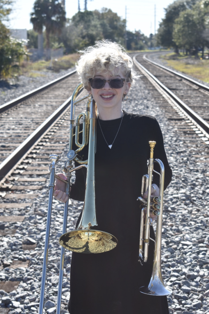 Lighthouse Transition student, Izzi Guzman, holding a trombone and a trumpet
