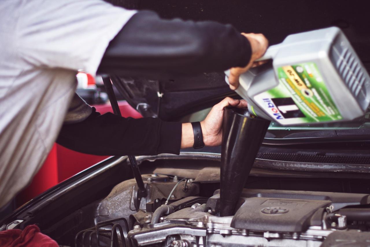 mecanico troca o oleo do motor do carro
